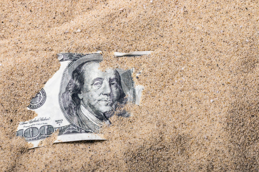 $100 dollar bill buried in sand depicting hospital finance