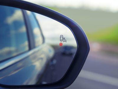 Blind Spot Monitoring system warning light icon in side view mirror of a modern vehicle.